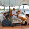 60′ Flybridge Guests eating and being served by Captain