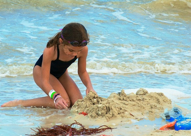 Girl on beach building sandcastle